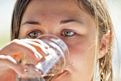 Teenage girl drinking. Impressive eyes of a teenage girl drinking a glass of water Stock Image