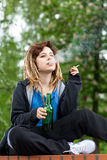 Teenage girl drinking beer and smoking cigarette Stock Photo