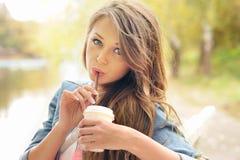 Teenage girl drinking coffee outdoor. Stock Photos