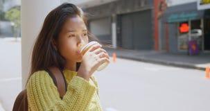 Teenage girl drinking coffee on street 4k