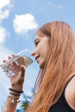 Teenage girl drinking a glass of water Stock Photos