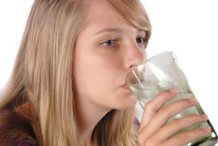 Teenage girl drinking ice water from a glass. Teenage healthy girl drinking ice water from a glass isolated on white studio shoot Stock Image