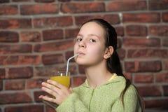 Teenage girl drinking orange juice Stock Images