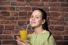 Teenage girl drinking orange juice stock images