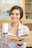 Teenage girl is drinking tea and reading Royalty Free Stock Photography