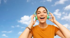 Teenage girl in earphones over sky royalty free stock images