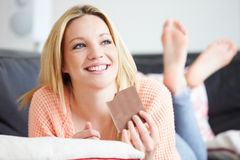Teenage Girl Eating Bar Of Chocolate At Home. Whilst Lying On Sofa Looking Away From Camera Stock Photos