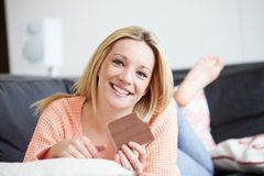 Teenage Girl Eating Bar Of Chocolate At Home. Whilst Lying On Sofa Looking To Camera Smiling stock photo