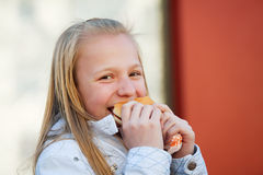Teenage girl eating a burger Royalty Free Stock Images