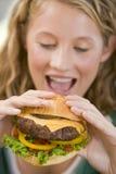 Teenage Girl Eating Burgers Royalty Free Stock Images