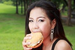 Teenage Girl Eating a Cheeseburger Stock Photography