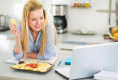 Teenage girl eating chips and looking in laptop Stock Photos
