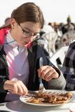 Teenage girl eating a delicious pancake with banana and chocolate in mountains. A restaurant placed on a ski slope. In French Alps royalty free stock photos