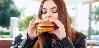 Teenage girl eating a hamburger. Portrait of a teenage girl eating a hamburger royalty free stock images