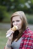 Teenage girl eating ice cream. Outdoors Stock Image