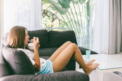 Teenage girl eating brekfast on couch in living room stock images