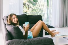 Teenage girl eating brekfast on couch in living room stock image