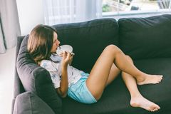 Teenage girl eating brekfast on couch in living room stock photos