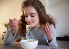 Teenage girl eating noodles at home Stock Images