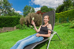 Teenage girl eating popsicles in a deckchair Royalty Free Stock Photography