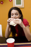 Teenage girl eating a sandwich Stock Images
