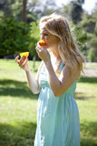 Teenage Girl Eating Sour Orange. A teenage girl, white, taking a taste of a wild orange she has picked from a nearby tree.  Her puckered expression demonstrates Stock Images