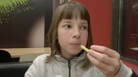 A teenage girl eats French fries for dinner at a fast food cafe.  stock footage