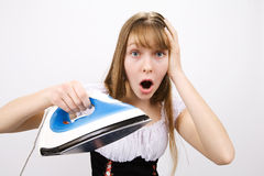 Teenage girl with electric iron Royalty Free Stock Photography