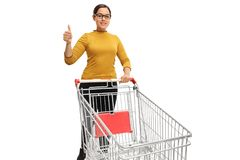 Teenage girl with an empty shopping cart making a thumb up gestu Stock Image