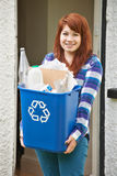 Teenage Girl Emptying Recycling At Home Stock Photo