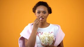 Teenage girl enjoying comedy series on tv eating popcorn on orange background. Stock photo royalty free stock photos