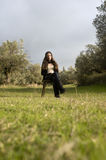 Teenage girl sitting on a chair in the countryside Royalty Free Stock Photography