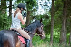 Teenage girl equestrian with smartphone riding horse taking picture. Bay horse with young teenage girl equestrian with smartphone riding horseback and taking stock photography