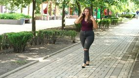 Portrait of a fat girl with long hair in the Park. A teenage girl with excess weight walks in the green park along the alley and talks on the phone stock video
