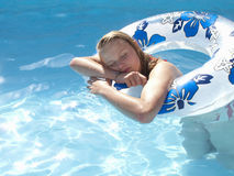 Teenage girl with eyes closed leaning on inflatable ring in swimming pool Stock Photo