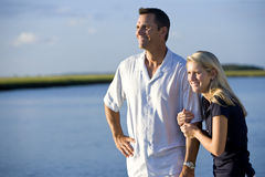 Teenage girl and father standing by water watching Stock Photography