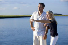 Teenage girl and father standing by water watching Royalty Free Stock Image