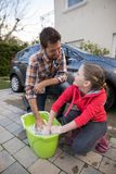Teenage girl and father washing a car Royalty Free Stock Photos