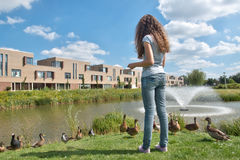 Teenage girl feeding ducks Royalty Free Stock Photography