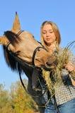 Teenage girl feeding horse Stock Photo