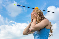 Teenage girl feeling fear with apple and arrow on head Royalty Free Stock Images
