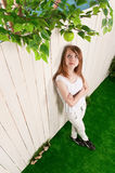 Teenage girl at the fence in the garden Royalty Free Stock Photo