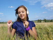 Teenage girl in a field listening music Royalty Free Stock Photos