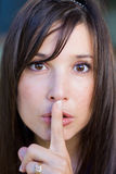 Teenage girl with finger on lips Stock Photos