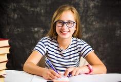 Teenage girl finishing homework at home. Teenage girl finishing homework assignment at home royalty free stock images