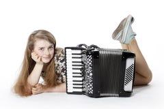 Teenage girl on the floor of studio with accordion royalty free stock image