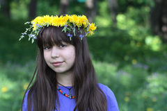 Teenage Girl And Flower Wreath. Nice teenage girl and wreath made from yellow dandelions on forest background Royalty Free Stock Photos