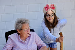 Teenage girl fools about with  her grandma Royalty Free Stock Image