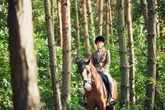 Girl riding a horse in forest. Teenage girl in formal wear riding a horse in forest Royalty Free Stock Photos