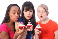 Teenage girl friends blowing out birthday candles